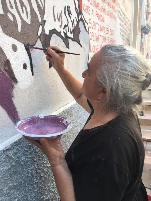 Anziana di Orgosolo che restaura i murales